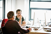 Coworkers discussing project in high tech office