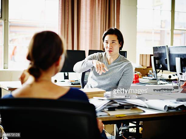 Coworkers discussing project in office