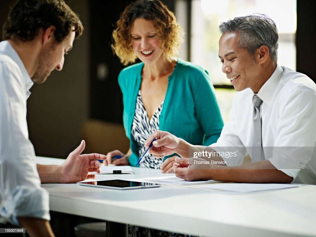 Coworkers discussing project in office smiling : Stock Photo