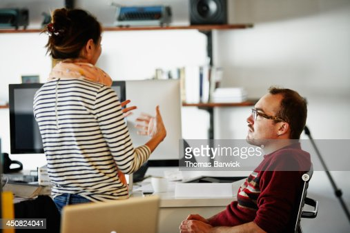 Coworkers discussing project in startup office : Stock Photo