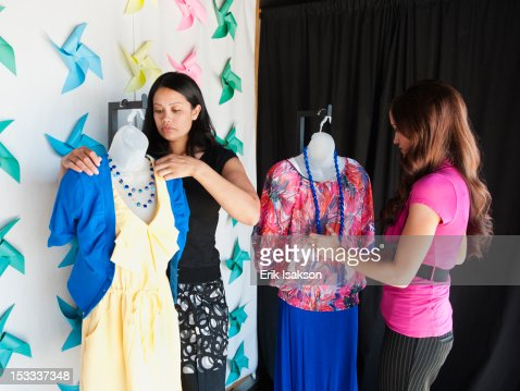 Co-workers dressing mannequins in store : Stock Photo