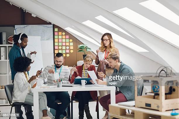 Kollegen essen Fast Food im Büro ihrer Inbetriebnahme.