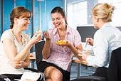 Coworkers eating in office