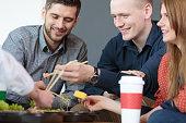 Cheerful coworkers enjoying their healthy, oriental meal