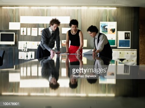 Coworkers examining documents at office table : Stock Photo