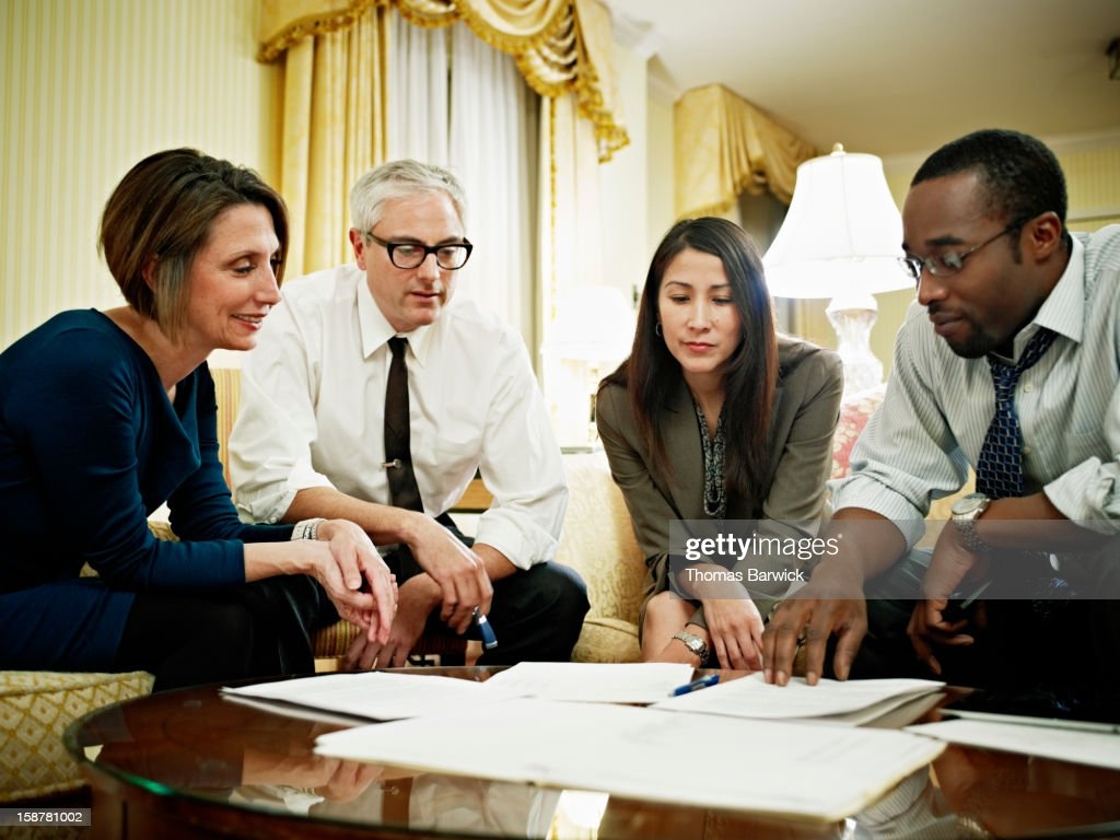 Coworkers examining project documents in hotel : Stock Photo