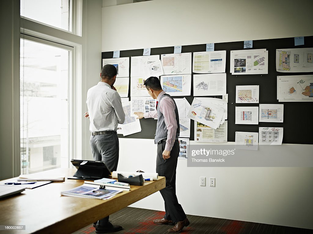 Coworkers examining project on board in office