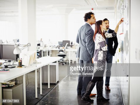 Coworkers examining project on wall of office