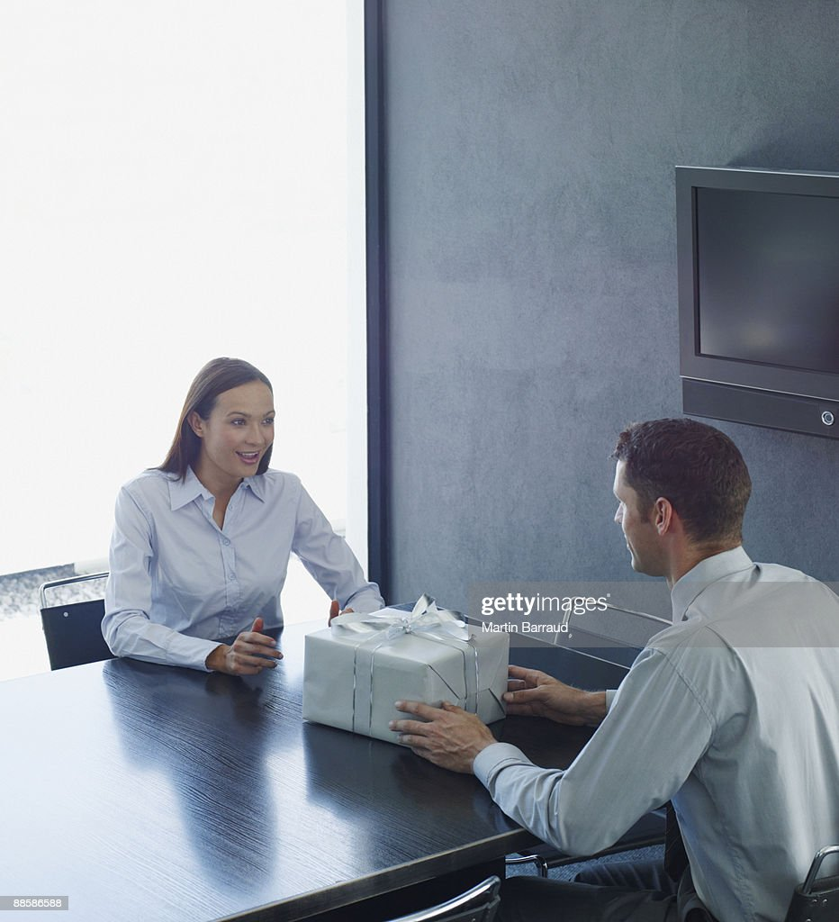 Co-workers exchanging gift in conference room : Stock Photo