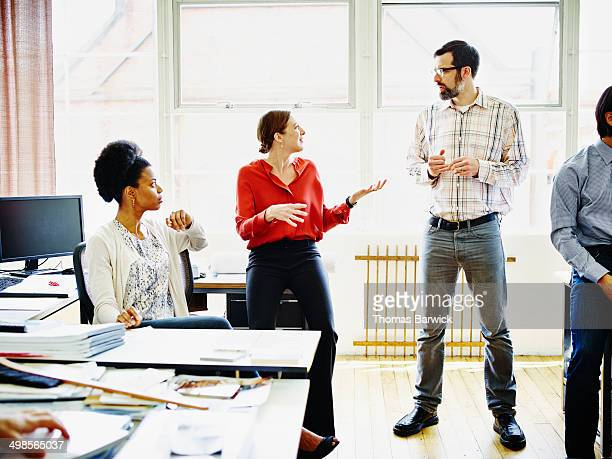 Coworkers having project discussion in office