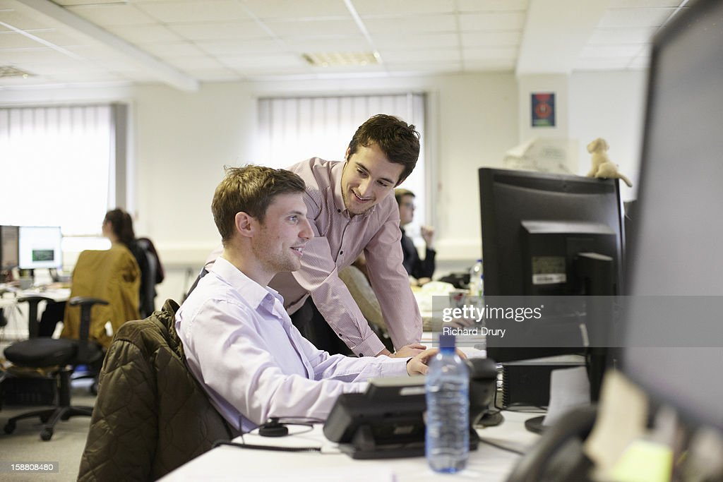 Coworkers in conversation in office : Stock Photo