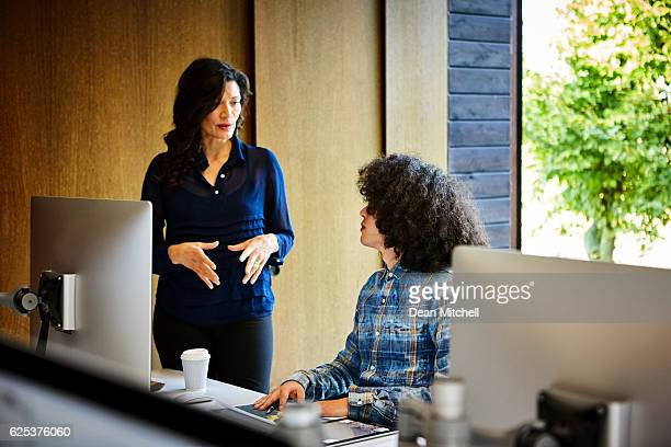 Coworkers in discussion at desk in office