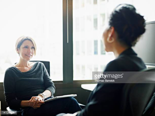 Coworkers in discussion at workstation in office