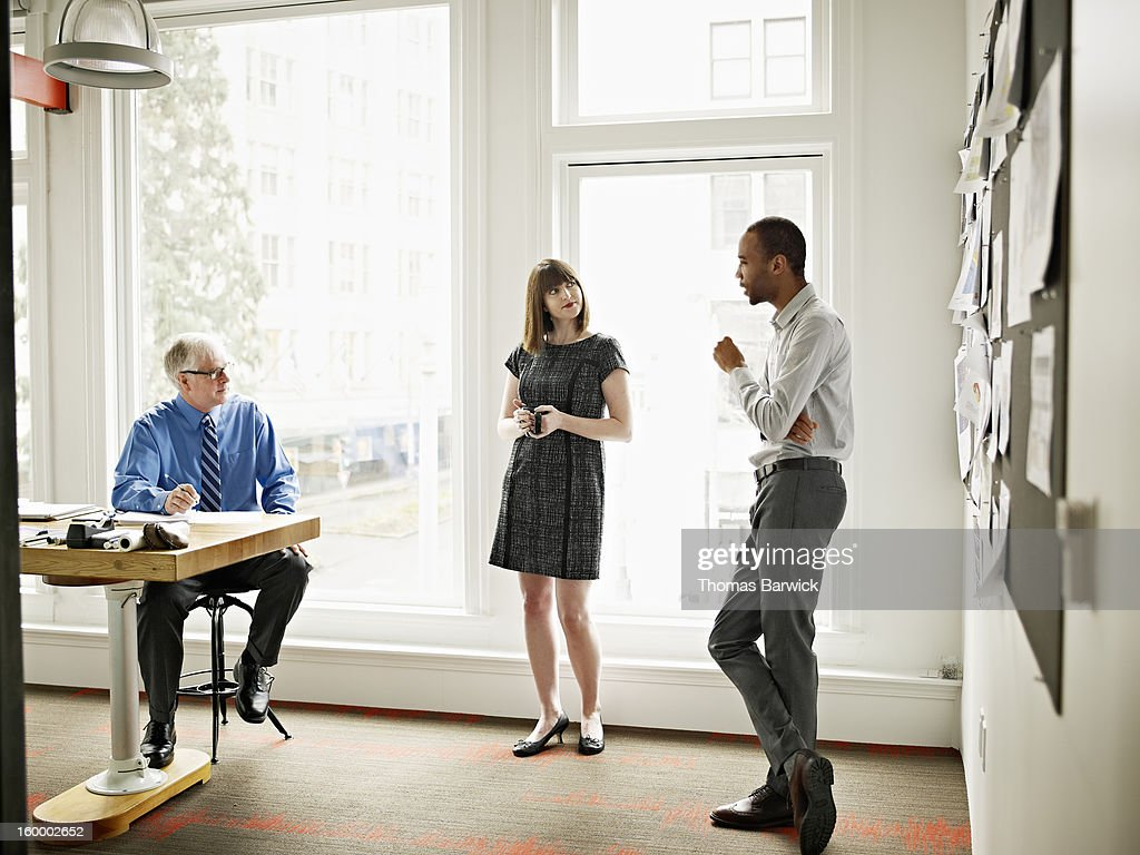 Coworkers in discussion in conference room : Stock Photo