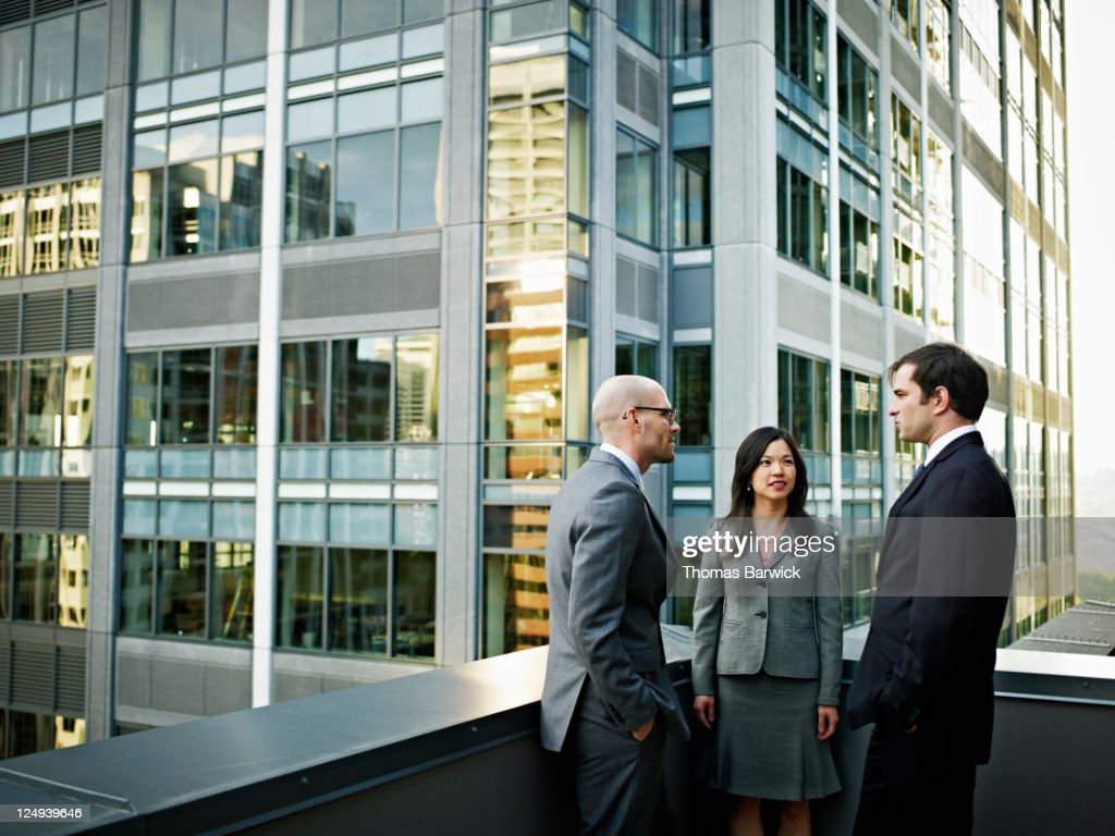 Coworkers in discussion in front of buildings : Stock Photo