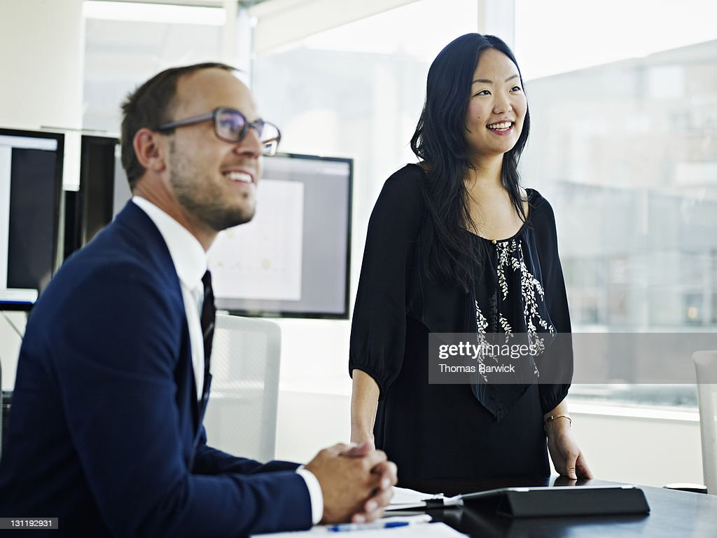 Coworkers in discussion looking up smiling : Stock Photo