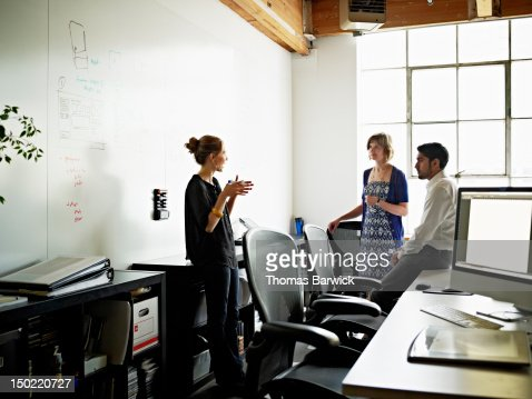 Coworkers in discussion over project in office