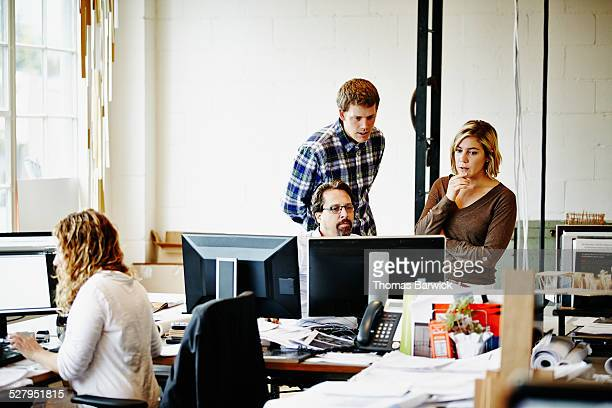 Coworkers in impromptu meeting discussing project