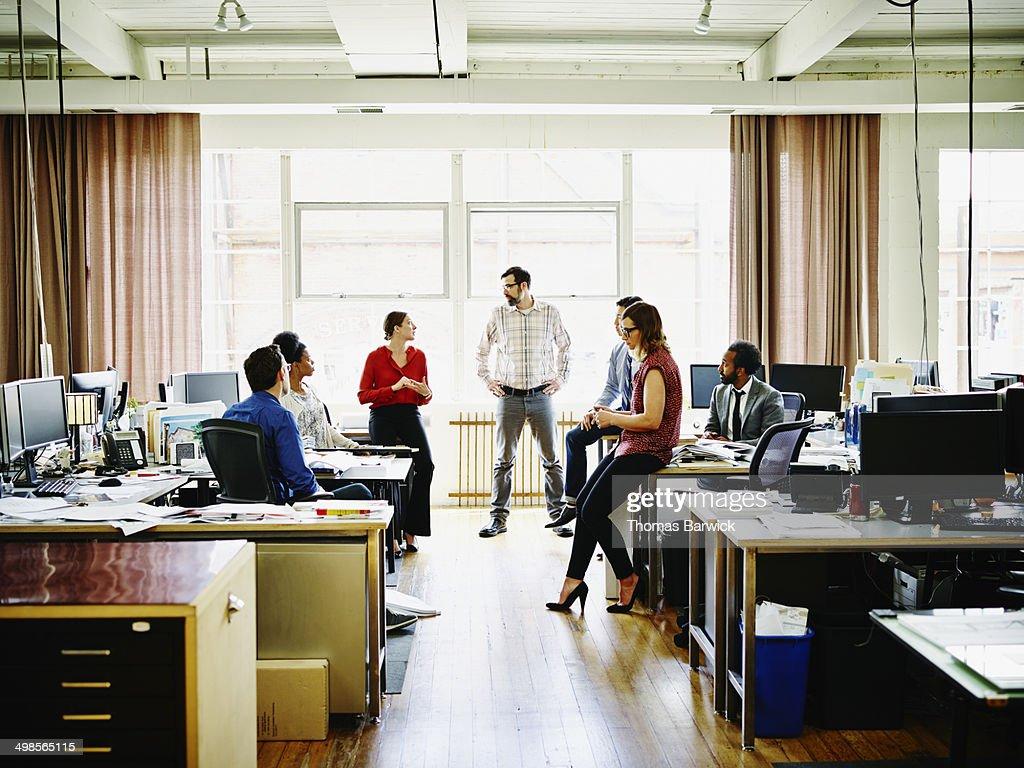 Coworkers in informal group meeting in office