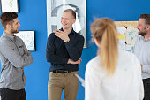 Group of coworkers listening closely to their colleague