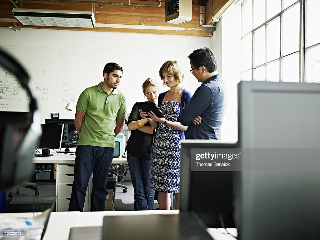 Coworkers looking at digital tablet in office : Stock Photo
