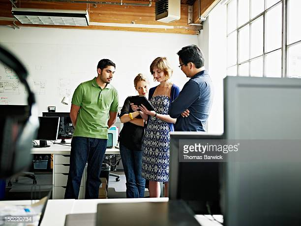 Coworkers looking at digital tablet in office