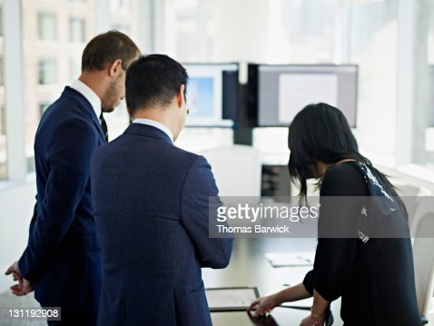 Coworkers looking at digital tablet rear view : Stock Photo
