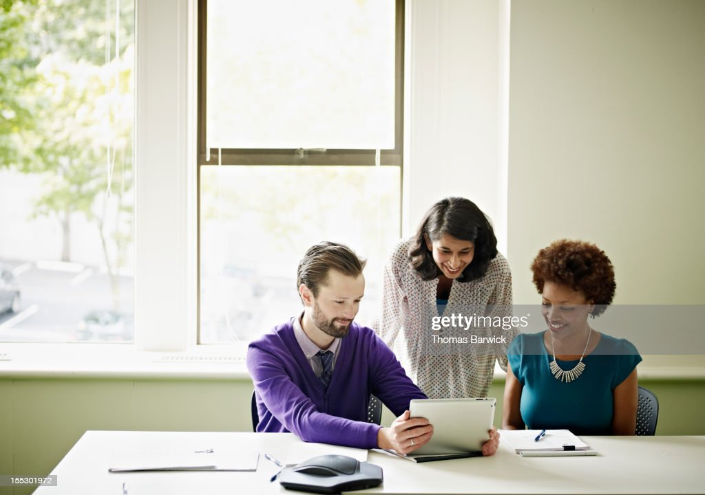 Coworkers looking at digital tablet smiling : Stock Photo
