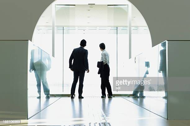 Coworkers looking out window in entrance hallway