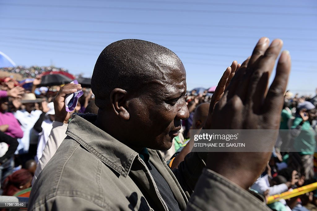 Co-workers of 34 miners shot dead by South African police during a violent wage strike pray during a ceremony to mark the first anniversary of their deaths on August 16, 2013 in Marikana. Today marks a year after police opened fire on thousands of strikers at platinum producer Lonmin's mine, northwest of Johannesburg, which killed 34 and injured 78 people. The August shooting was described as the worst police brutality since the end of apartheid two decades ago. Three days ago, the firm has recognised radical labour group AMCU, which led the wage strike, in an attempt to ease simmering inter-union tensions on the platinum belt. AFP PHOTO / STEPHANE DE SAKUTIN