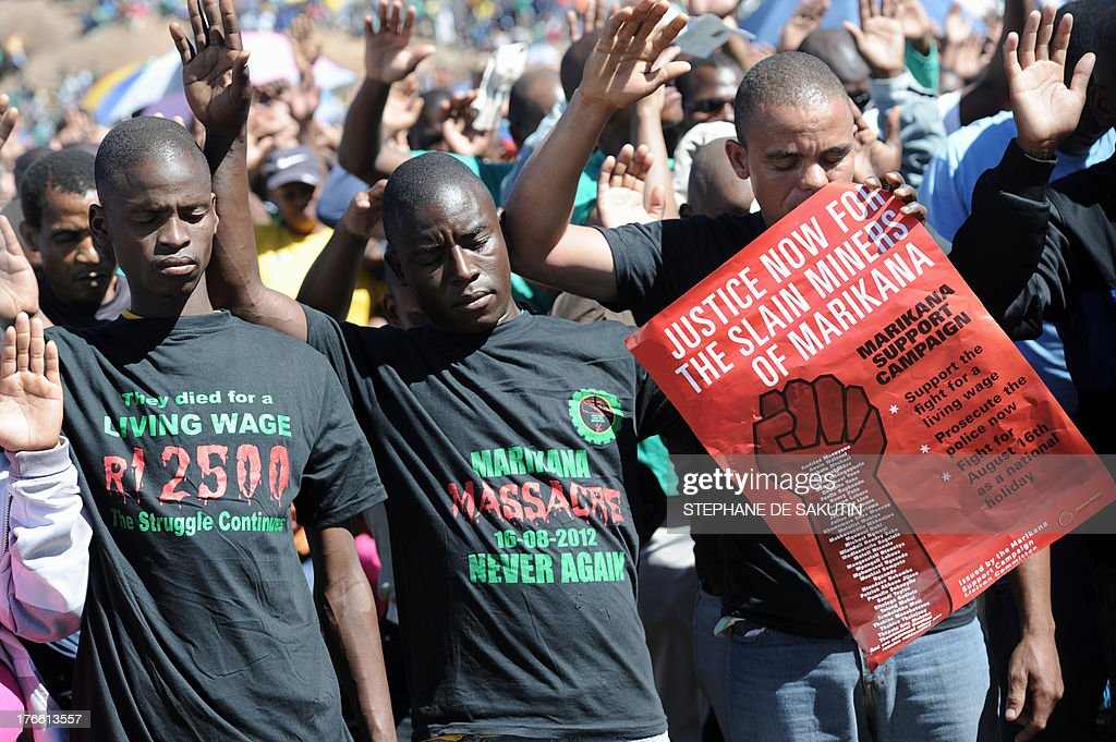 Co-workers of 34 miners shot dead by South African police during a violent wage strike pray during a ceremony to mark the first anniversary of their deaths on August 16, 2013 in Marikana. Today marks a year after police opened fire on thousands of strikers at platinum producer Lonmin's mine, northwest of Johannesburg, which killed 34 and injured 78 people. The August shooting was described as the worst police brutality since the end of apartheid two decades ago. Three days ago, the firm has recognised radical labour group AMCU, which led the wage strike, in an attempt to ease simmering inter-union tensions on the platinum belt.