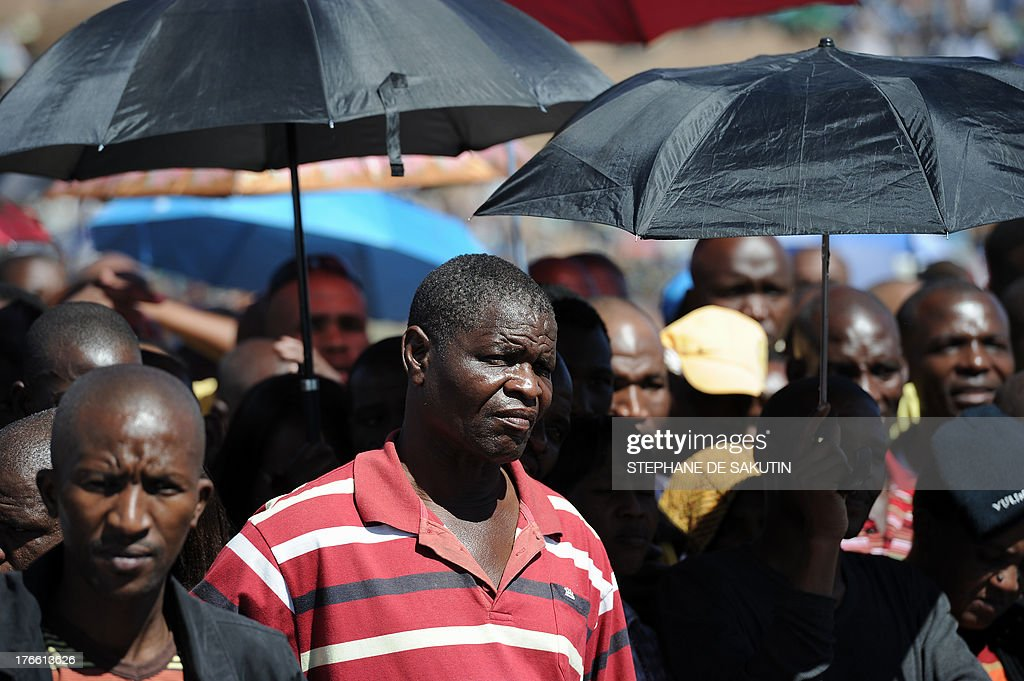 Co-workers of 34 miners shot dead by South African police during a violent wage strike attend a ceremony to mark the first anniversary of their deaths on August 16, 2013 in Marikana. Today marks a year after police opened fire on thousands of strikers at platinum producer Lonmin's mine, northwest of Johannesburg, which killed 34 and injured 78 people. The August shooting was described as the worst police brutality since the end of apartheid two decades ago. Three days ago, the firm has recognised radical labour group AMCU, which led the wage strike, in an attempt to ease simmering inter-union tensions on the platinum belt.
