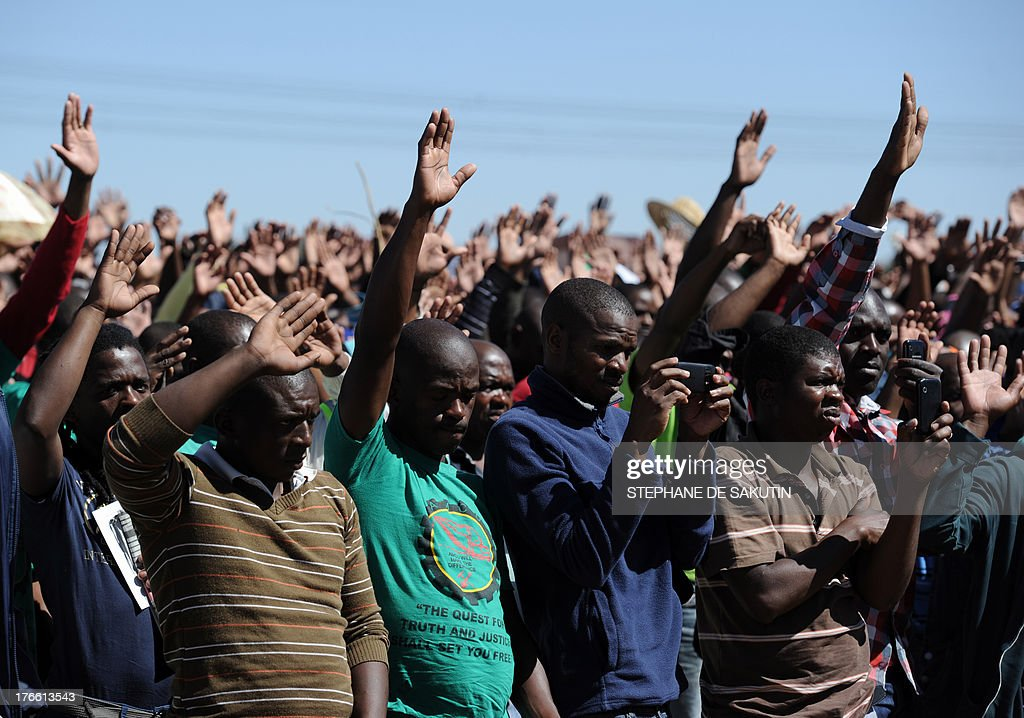 Co-workers of the 34 miners shot dead by South African police during a violent wage strike attend a ceremony to mark the first anniversary of their deaths on August 16, 2013 in Marikana. Today marks a year after police opened fire on thousands of strikers at platinum producer Lonmin's mine, northwest of Johannesburg, which killed 34 and injured 78 people. The August shooting was described as the worst police brutality since the end of apartheid two decades ago. Three days ago, the firm has recognised radical labour group AMCU, which led the wage strike, in an attempt to ease simmering inter-union tensions on the platinum belt.