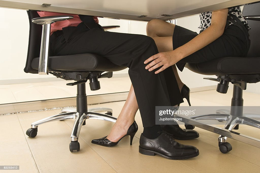 coworkers playing footsie under table stock photo getty images. Black Bedroom Furniture Sets. Home Design Ideas