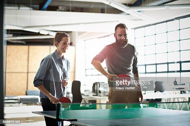 Co-workers playing tabletennis at the office