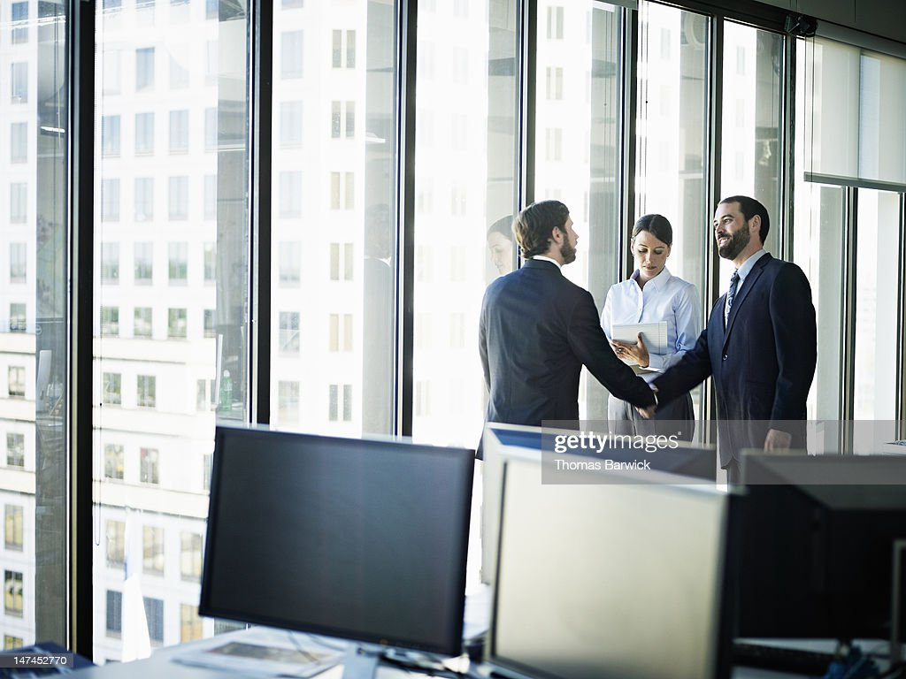 Coworkers shaking hands near windows in office : Stock Photo