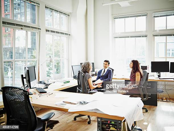 Coworkers sitting in office discussing project
