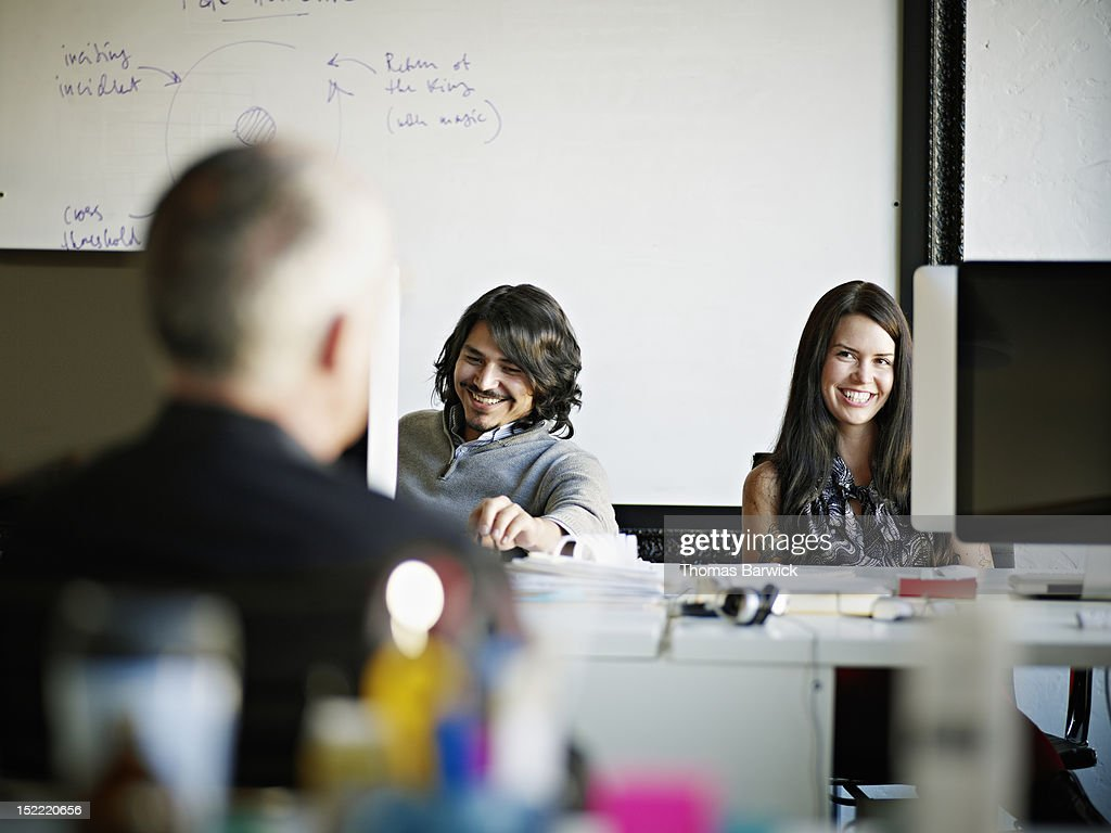Coworkers sitting in office in discussion : Stock Photo