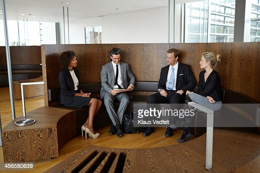 Coworkers sitting together in business lounge : Stock Photo