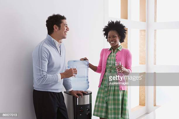 Co-workers smiling by water cooler