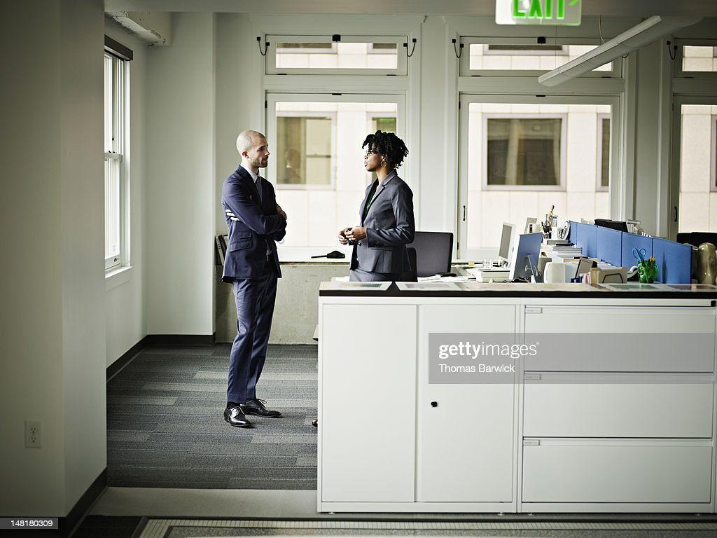 Coworkers standing at workstation in discussion : Stock Photo