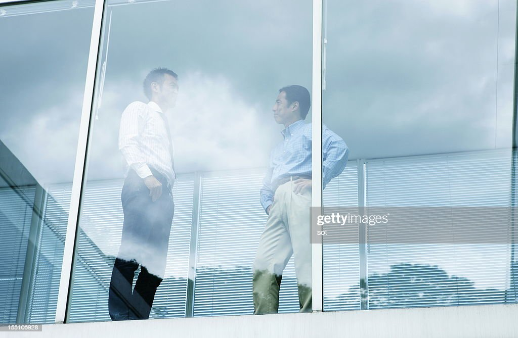 Coworkers standing near windows in office hallway : Stock Photo