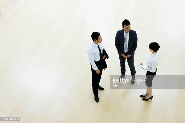 Coworkers talking in entrance hall of office