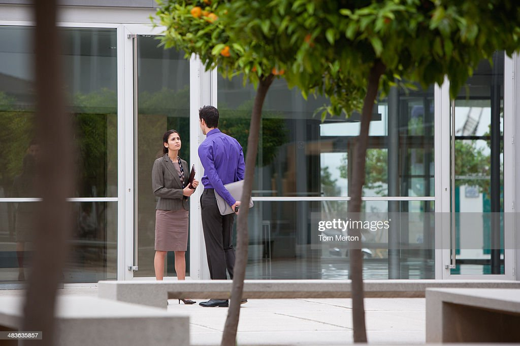 Co-workers talking in office building courtyard : Stock Photo
