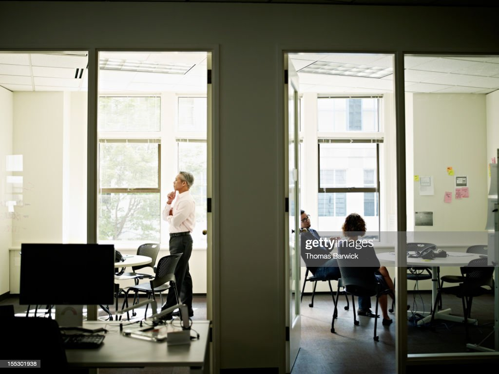 Coworkers working in adjoining conference rooms : ストックフォト