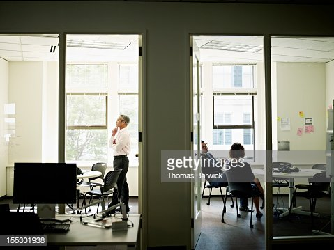 Coworkers working in adjoining conference rooms : Stock Photo