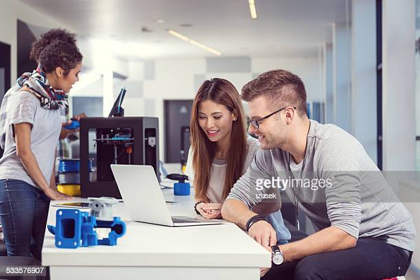 Collègues travaillant sur un ordinateur portable sur l'imprimante de bureau 3d