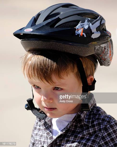 DENVER COYoung Cooper Akin straps on an undersized bike helmet but later puts on one that firs before heading out to the Bike Rodeo course set up at...