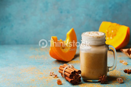 Cozy breakfast or snack from pumpkin spiced latte or coffee in glass on turquoise vintage table. Fall or winter hot drink. : Foto de stock