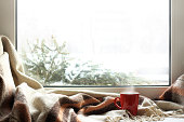 red mug of hot drink on a windowsill with a warm blanket, when behind is window is snow